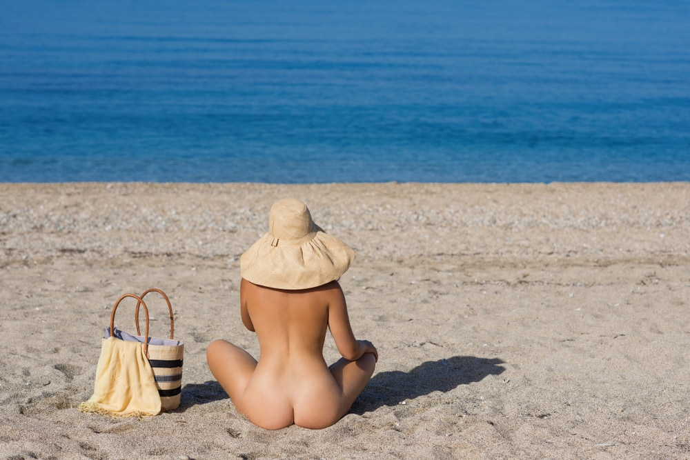 Nudist female sitting on the beach with hat on